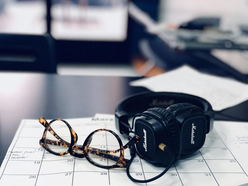headphones and glasses on desk calendar