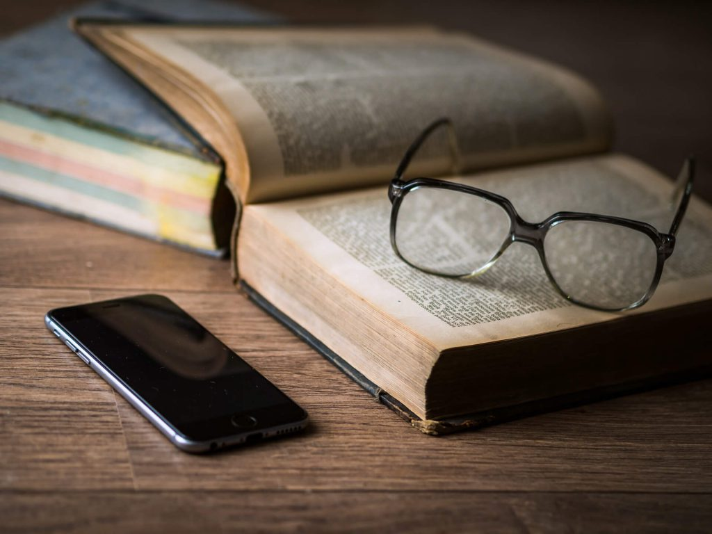 glasses on open book near phone